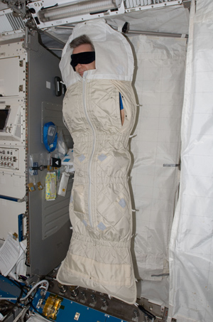 Astronaut Robert Thirsk, asleep in his sleeping quarters in the ISS. Photo credit NASA.